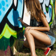 Stock Photo: Beautiful girl is drawing graffiti