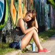 Girl near wall with graffiti — Stock Photo