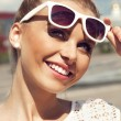Foto Stock: Portrait of beautiful blonde girl in sunglasses on background blue sky
