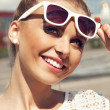 Portrait of beautiful blonde girl in sunglasses on background blue sky — Stock Photo