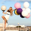 Stock Photo: Happy young womwith colorful latex balloons