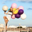 Happy young woman with colorful latex balloons — Stock Photo