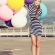 Happy young woman with colorful latex balloons — ストック写真