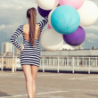 Happy young womwith colorful latex balloons — Stock Photo #36810889