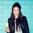 Young woman eating ice cream over blue brick wal — Stock Photo