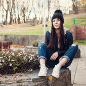 Teen girl sitting on stairs against grunge wall — Stockfoto