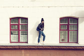 Young woman walking on cornice — Stock Photo