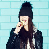 Young woman eating ice cream over blue brick wal — Foto de Stock