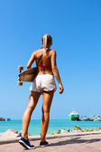 Woman walking and holding a longboard — Stock Photo