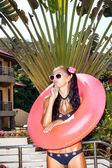 Frau im weißen sonnenbrillen mit rosa schlauch — Stockfoto