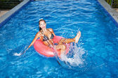 Woman floating in inner tube in pool and having fun — Stock Photo