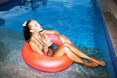 Woman floating in inner tube in pool and drinking water — Stock Photo