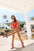 Meisje in zonnebril met longboard — Stockfoto