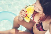 Girl eating watermelon against swimming pool — Stock Photo