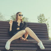 Young woman smoke in park — Stock Photo