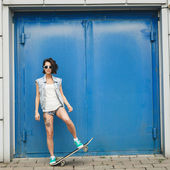 Young brunette woman posing with skateboard — Stock Photo