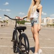 Beautiful young woman with bike outdoors — Stock Photo #48719683