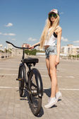 Beautiful young woman with bike outdoors — ストック写真