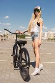 Schöne junge Frau mit Motorrad im freien — Stockfoto