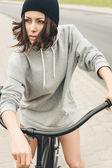 Young hipster girl with black bike — Stock Photo