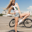 Young sexy woman with bike outdoors — Stock Photo