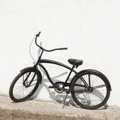 Black city bicycle cruiser standing by next white wall — Photo