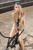 Beautiful young woman with bike outdoors — Stock Photo