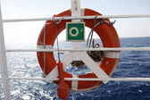 Red Life buoy in front of the blue sea and the white ship — Stock Photo