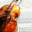 Old violin lying on the sheet of music — Stock Photo #40027965