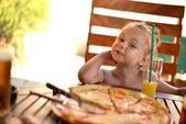 Happy little girl eating pizza — Stock Photo