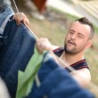 Down syndrome man hanging clothes - Stock Photo