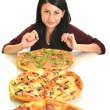 Young woman eating a piece of pizza against a white background — 图库照片