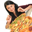 Young woman eating a piece of pizza against a white background — Stock Photo