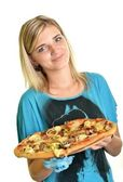 Young woman eating a piece of pizza against a white background — Стоковое фото