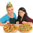 Beautiful girls eating pizza for lunch — Stock Photo