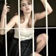 Beautiful teenager girl behind the metal bar — Stockfoto
