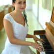 Beautiful young attractive woman in cocktail dress and piano — Stock Photo #13637939