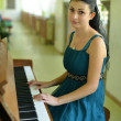 Beautiful young attractive woman in cocktail dress and piano — Stockfoto