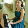 Beautiful young attractive woman in cocktail dress and piano — Stok fotoğraf