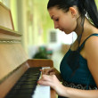 Woman playing piano — Stockfoto