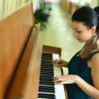 Beautiful young attractive woman in cocktail dress and piano — Stock fotografie
