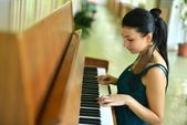 Beautiful young attractive woman in cocktail dress and piano — Stock Photo