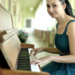 Beautiful young woman playing the piano — Stock Photo