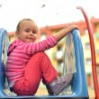 Attractive little girl on outdoor playground equipment — Stock Photo