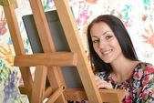 Beautiful woman painting with a paintbrush — Stock Photo
