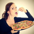 Royalty-Free Stock Photo: Portrait of a young woman eating a pizza over a white background