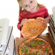 Little girl eating pizza - Stock Photo