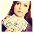 Pretty woman holding fan made of money and contemplating - Stock Photo