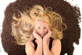 Portrait of a girl's face drowned in coffee beans — Stok fotoğraf