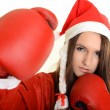 Christmas woman hitting wearing boxing gloves and red santa hat - Zdjęcie stockowe
